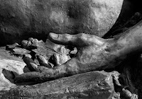 statue detail of a hand and some leaves resting on a rock