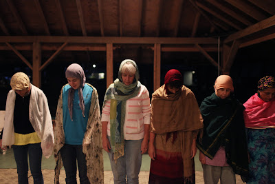 six women with head scarves stand ready for prayer