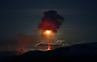 erupting volcano at night under full moon