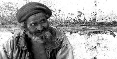 An old man with beard smiling.