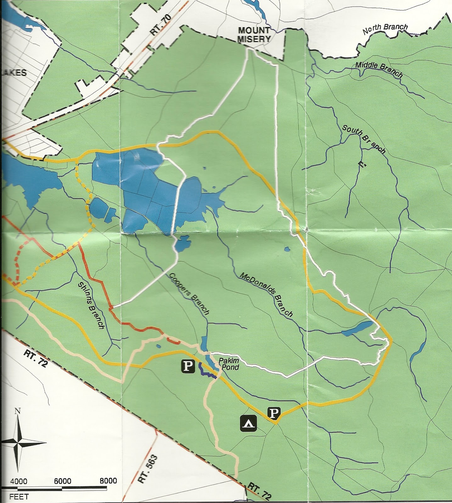 the yellow trail on the map which shown as a bike trail is actually thesame as a paved road (shinns road) which goes through the park. gone hikin' brendan t byrne state forest nj  mt misery trail