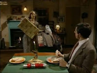 Image: Mr. Bean sits at a table laden with two plates –each with a sandwich and some carrots–, a Christmas cracker, and a Christmas candle. Mr. Bean is looking away from the camera towards Irma, who holds a rather large Christmas present for him.