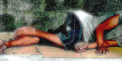 Homeless man sleeping on cardboard outside