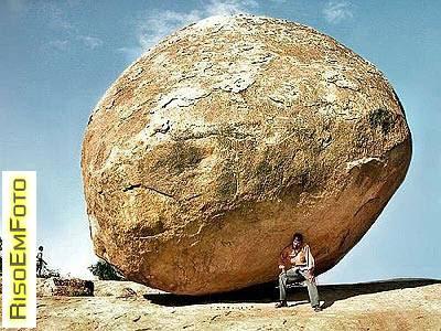 Fotografia de turista que simula sustentar uma enorme pedra.