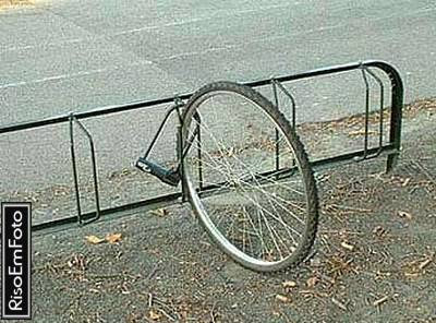 Foto mostra a roda da frente de bicicleta roubada, presa por trava.