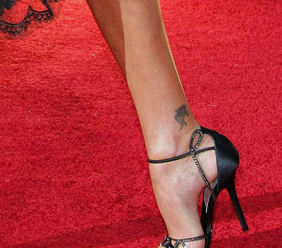 She has also a small flower tattoo above her right foot.