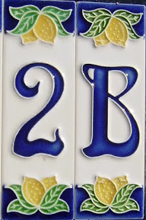 ceramic tiles with the house number 2B in blue on a creamy white background and decorated with lemons top and bottom