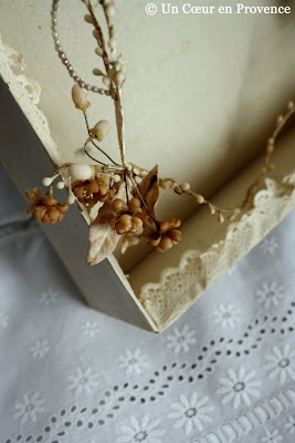Old bridal ornaments in original box whose contour is festooned with lacy paper