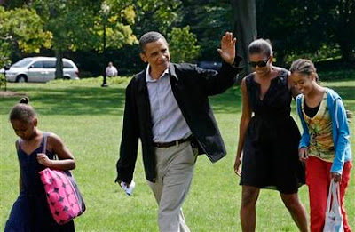President Barack Obama and first lady Michelle Obama, with daughters Malia and Sasha, left, return to the White House in Washington after five days at Camp David Sunday, Sept. 6, 2009.