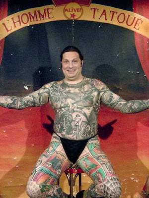 Body Art Tattoo Comic story tattooed on fat man's body .