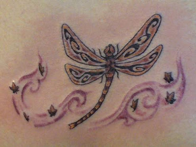 Pretty Celtic dragonfly tattoo surrounded by little flowers.