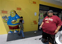 Steve Aragon, 30, gets ready to take a picture of his sons Giovanni, 7, and Esteban, 4, outside the 7-Eleven in Burbank, Calif. Monday, July 2, 2007. Over the weekend, 7-Eleven Inc. turned a dozen stores into Kwik-E-Marts, the fictional convenience stores of the television show