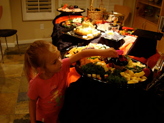 Little girl reaching for a snack at a table full of food