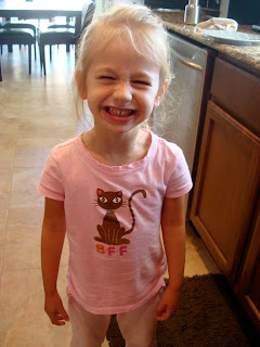 Little girl standing in the kitchen smiling