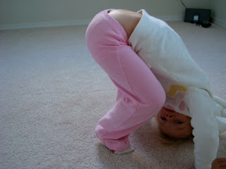 Young girl attempting downward dog yoga pose
