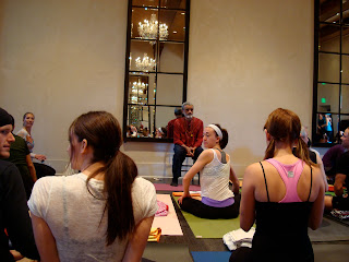 Dharma Mittra talking to room full of people on yoga mats
