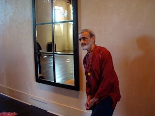 Dharma Mittra standing in front of wall