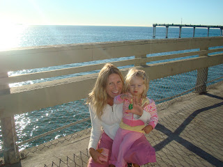 Woman and child on pier crouching showing ocean in background