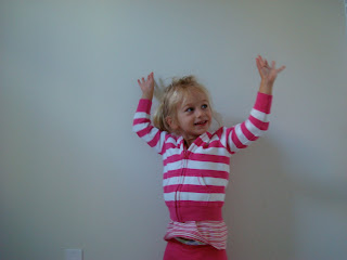 Young girl standing in front of wall with arms up