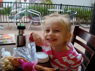 Young girl sitting at table smiling with toys and snacks