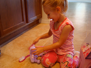 Young girl playing with purple small teddy bear