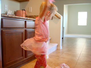 Young girl dancing in kitchen dancing in pink tutu