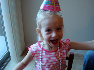 Young girl smiling in birthday hat and beaded necklace
