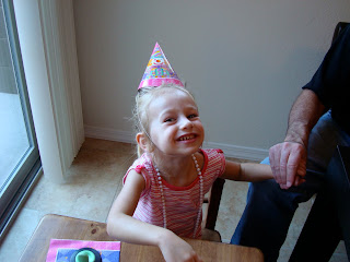 Young girl smiling wearing birthday hat holding mans hand