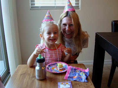 Young girl and woman standing at table wearing birthday hats