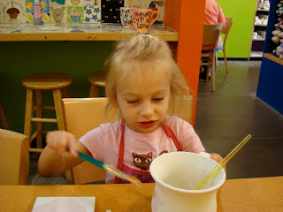 Young girl in pink painting a coffee mug
