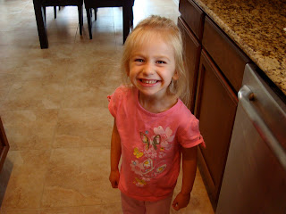 Young girl in pink standing and smiling in kitchen
