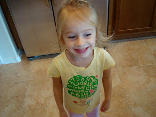 Young girl in yellow t-shirt standing in kitchen