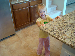 Young girl in pink and yellow in kitchen holding onto countertop