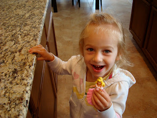 Young girl holding doll in kitchen smiling