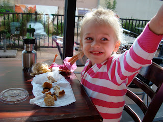 Young girl at coffee shop at table pointing with snacks in front of her