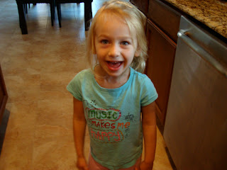 Young girl in blue shirt in kitchen smiling