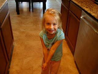 Young girl grasping hands in kitchen
