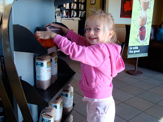 Young girl touching coffee display at Starbucks