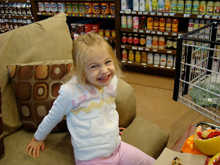 Young girl giving large smile while sitting on oversized chair