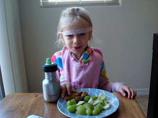 Young girl with headband above eyes eating snacks
