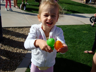 Young girl holding green and orange Easter eggs