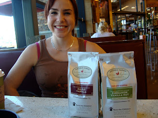 Woman sitting in booth with two packages of coffee in front of her
