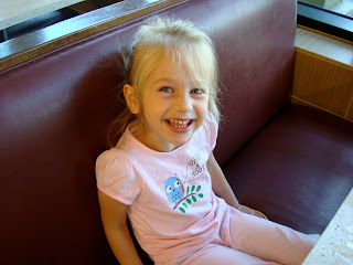 Young girl wearing pink with pony tail sitting in booth smiling