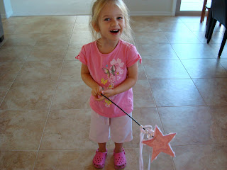 Young girl in pink holding princess wand
