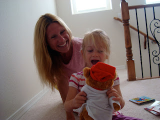 Woman and child smiling as she looks at stuffed animal