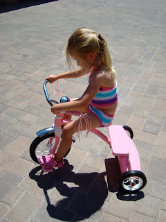 Side view of young girl riding tricycle