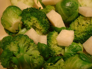 Broccoli with greens, jicama and Brussel sprouts in bowl