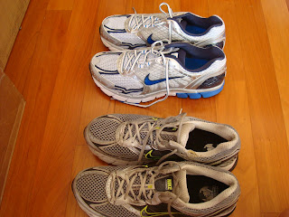 Two pairs of running shoes next to one another one old one new