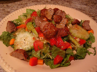 Salad in shallow bowl with chopped up meatballs