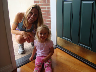 Woman and little girl smiling in front of a door